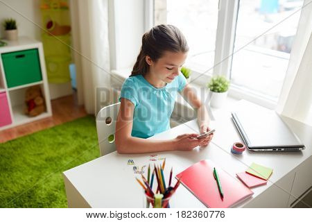 children, technology and communication concept - smiling girl distracting from homework and texting on smartphone at home