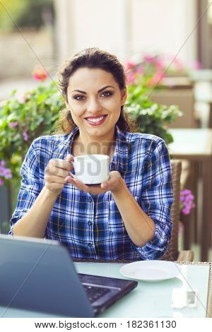Young happy smiling woman woking on computer outdoors