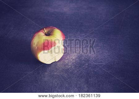 Color toned ripe bitten apple on a dark background selective focus space for text.