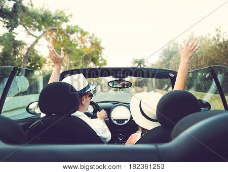Happy free couple in car driving in car cheering joyful with raised arms