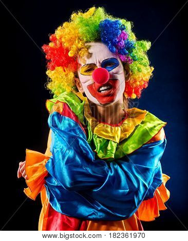 Sad clown on black background. Portrait of sick woman holds on to stomach after performance.
