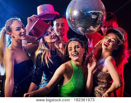 Dance party with group people dancing . Women and men have fun in night club. Happy girl on foreground and disco ball on background. Guys took off their hats.