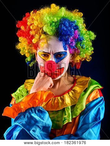 Sad clown on black background. Portrait of sick woman holds to cheek with toothache after performance.