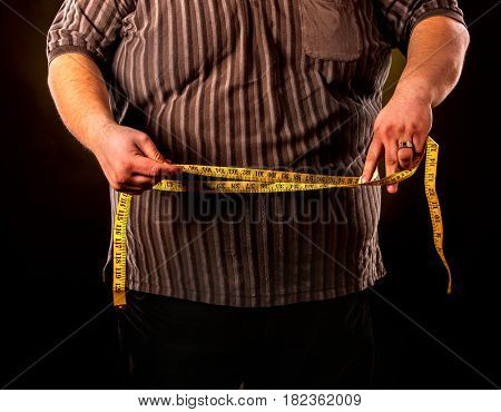 Man belly fat with tape measure weight loss around body on black background. Cropped shot of first day of diet.