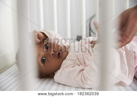 Close Up Of Baby Girl Lying In Nursery Cot