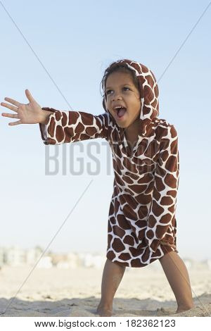 Young mixed race girl gesturing on beach wearing hoody