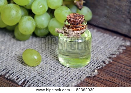 Grape seed oil in a glass jar and fresh grapes on old wooden table.Bottle of organic grape seed oil for spa and bodycare.Spa,Bio,Eco products concept.Soft selective focus.