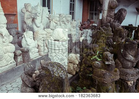 Sculptures, offerings and a hand-carved statue of the statues at a village in Ubud, Bali, Indonesia.