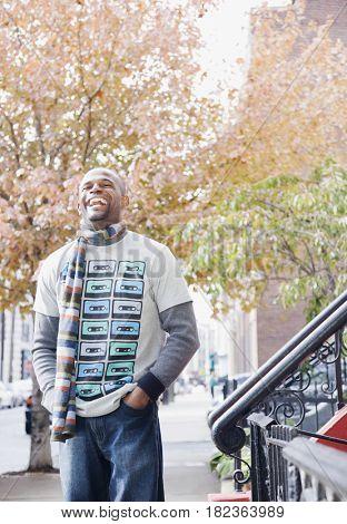 African man smiling on sidewalk