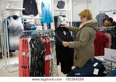 ENSCHEDE THE NETHERLANDS - APRIL 13 2017: A woman is shopping in clothes store C&A after it has been reopened.