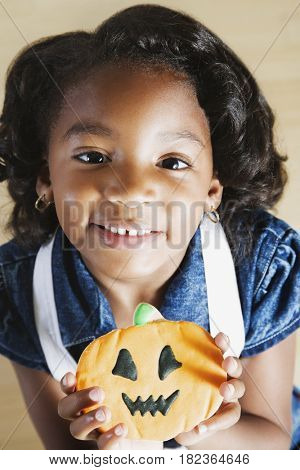 African girl holding Halloween cookie