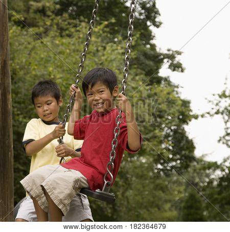 Asian boys swinging on playground