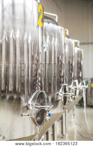 Brewery. Modern beer plant with brewering kettles, tubes and tanks made of stainless steel