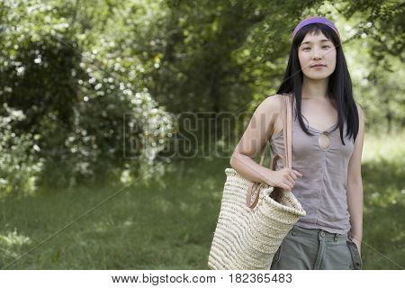 Asian woman holding large bag outdoors