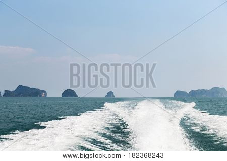 sailing, travel, tourism, seascape and nature concept - ocean and leaving boat trace on water