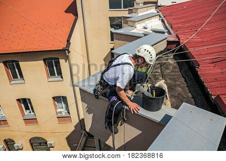 Young Window Cleaner Descend from the Roof of the Building. High Risk Work.