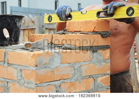 Bricklayer Bricklaying Concept. Bricklaying Tools. A bricklayer using a level to check his new house construction wall outdoor. Brickwork. Bricklaying Bricklayer Brickwork.