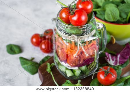 Fresh veggie vegetables salad in mason jar and ingredients. Healthy food and diet. Copy space.