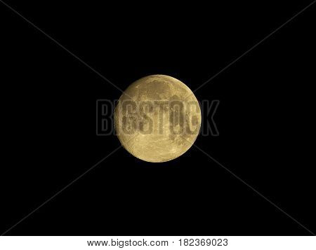 Full yellow moon in empty black sky, with visible mares and big craters.