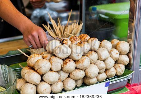 cooking, asian kitchen, people and food sale - seller hand with meatballs at street market