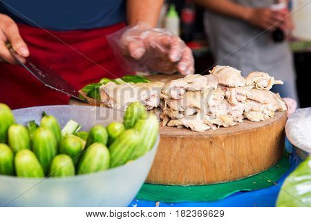 cooking, asian kitchen, people and food sale - cook with poultry and cucumbers at street market