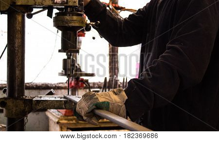 Construction worker drills hole in rod of metal iron using industrial drill in a bright workshop / workshed / factory
