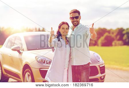 transport, road trip, travel, family and people concept - happy man and woman hugging at car and showing thumbs up