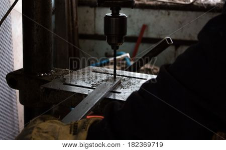 Construction worker drills hole in rod of metal iron using industrial drill in a dark dingy workshop / workshed / factory