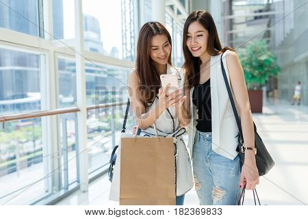 Young girls go shopping center and using cellphone together