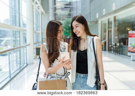 Young girls walking in shopping center and using cellphone together