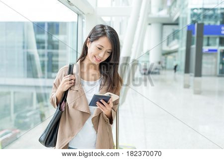 Woman looking at mobile phone in airport