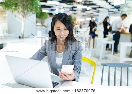Businesswoman working on cellphone and laptop computer in office
