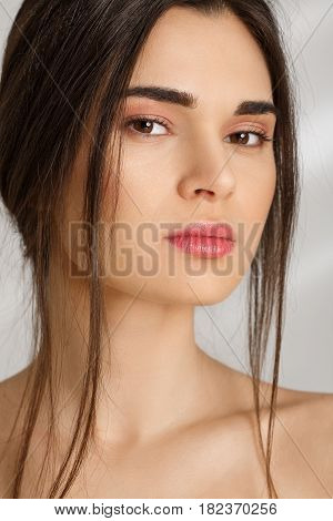 Closeup portrait of naked attractive woman with beautiful collarbone, natural make up on grey background.