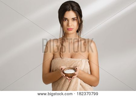 Young sensual woman in nice towel holding salt body scrub in hands, looking straight.