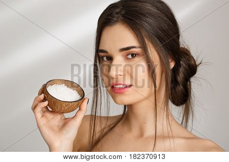 Closeup of beutiful naked woman showing salt scrub after spa procedures, looking straight at camera.