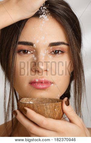 Closeup portrait of beautiful woman pouring body salt scrub, looking at camera. On grey background.