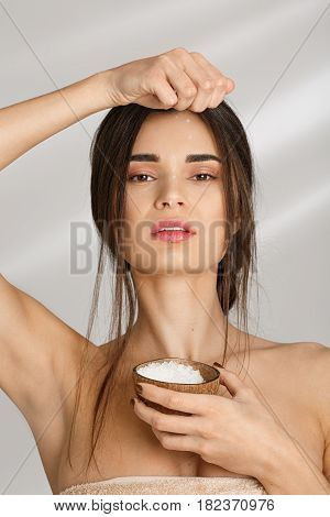 Vertical shot of beautiful woman in salt towel pouring salt body scrub, after prcedures.