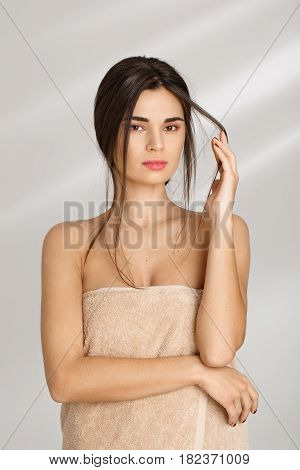 Spa concept. Sensual woman covered with soft towel holding strand of hair, looking straight.
