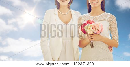 people, homosexuality, same-sex marriage and love concept - close up of happy married lesbian couple with flower bunch over sky and sun background