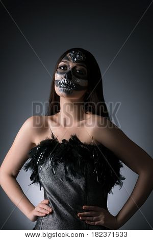 Woman with smart artistic makeup in horror style posing in corset with feathers in studio