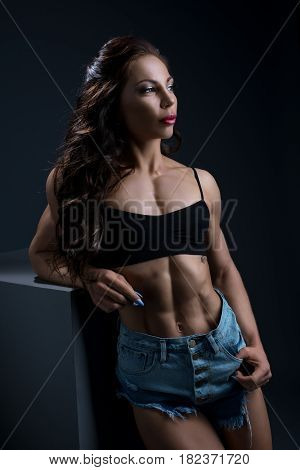 Athletic brunette posing in studio in jeans shorts and black sporty bra