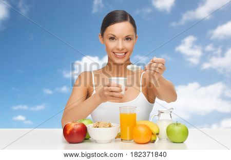 diet, healthy food and people concept - happy woman with fruits and cereals eating yogurt for breakfast over blue sky and clouds background