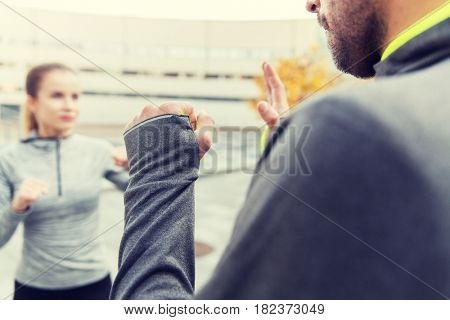fitness, sport, people, exercising and martial arts concept - close up of woman with trainer working out self defense strike on city street