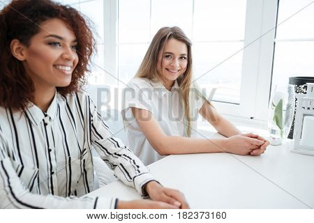 Side view of a two young women sitting by the table in cafe