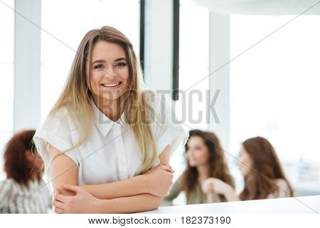 Happy Blonde woman standing by the table in cafe with her friends on background