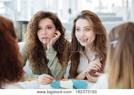 Two shocked women sitting by the table with their friends in cafe. Cropped image