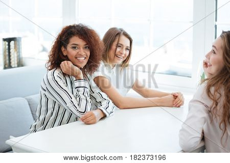 Side view of a three women sitting by the table in cafe