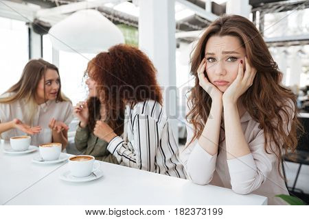 Side view of a young upset woman sitting by the table in cafe near her friends which say among themselves