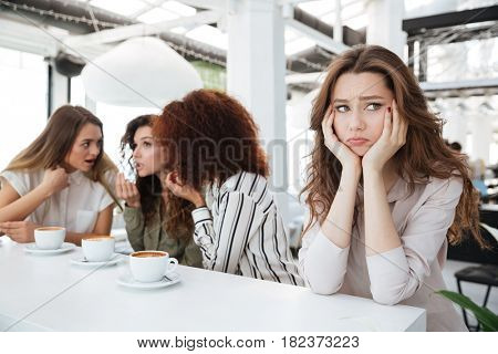 Side view of a upset woman sitting by the table in cafe near her friends which say among themselves