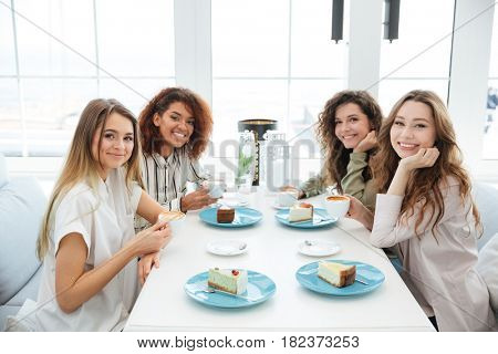 Side view of a four friends sitting by the table in cafe and looking at the camera